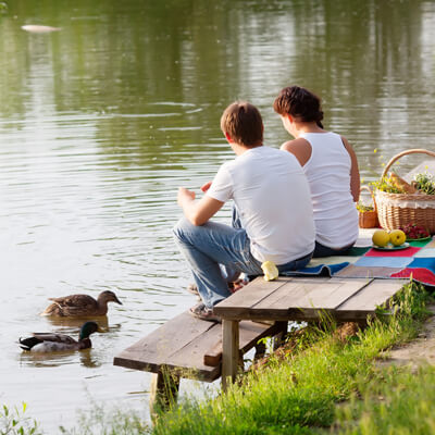 couple sitting on a picnic table by the lake
