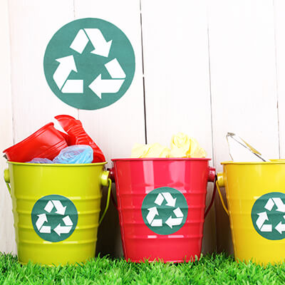 Three recycles bins on the grass
