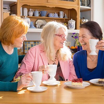 Three women discussing and having tea