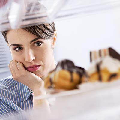 Lady looking at pastry with temptation