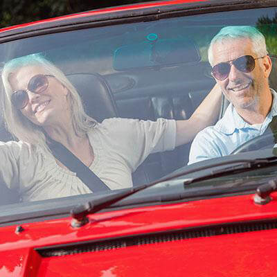Man and woman laughing in a car