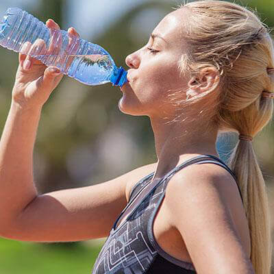 Girl drinking water on a sunny day