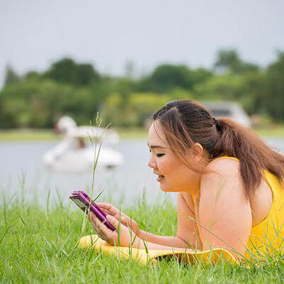 woman on grass with cellphone
