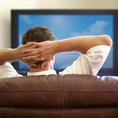 Man watching TV sitting on a couch