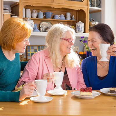 Three women discussing and having tea