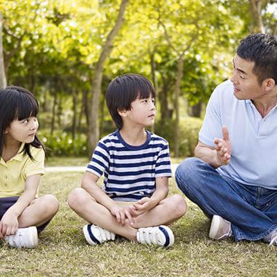 Un père est assis sur le gazon et discute avec ses enfants.